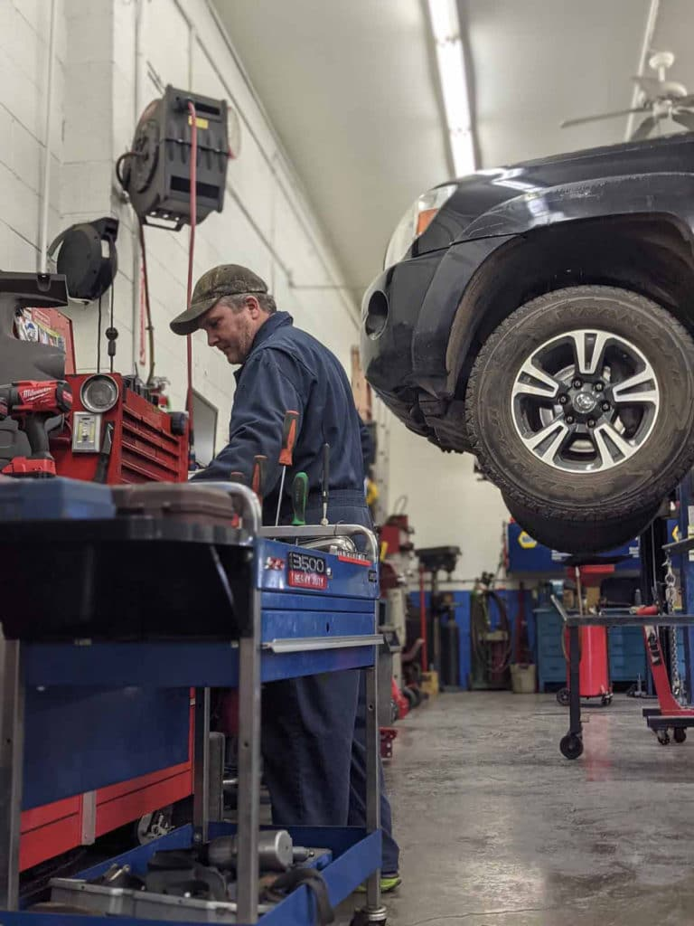 Technician looks for parts needed along tool bench against garage wall